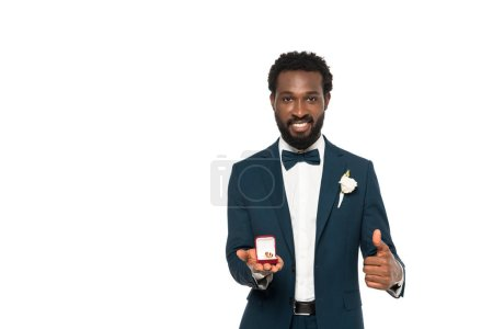 Photo for Cheerful african american man holding box with wedding ring and showing thumb up isolated on white - Royalty Free Image