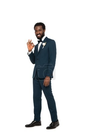 Photo for Happy african american bridegroom showing ok sign and standing isolated on white - Royalty Free Image