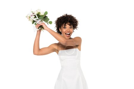 Photo for Excited african american bride throwing bouquet and looking at camera isolated on white - Royalty Free Image