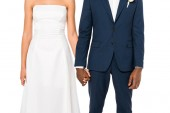 cropped view of african american bride and bridegroom holding hands while standing isolated on white