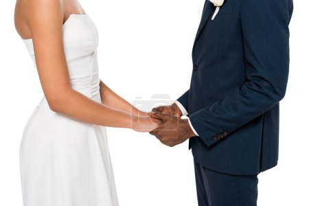 Photo for Cropped view of african american bride and bridegroom holding hands isolated on white - Royalty Free Image