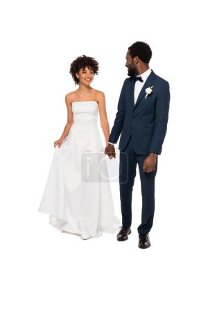 Photo for Happy african american bridegroom holding hands with beautiful bride in wedding dress isolated on white - Royalty Free Image