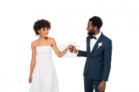 Photo for Happy african american bridegroom looking at bride while holding hands isolated on white - Royalty Free Image