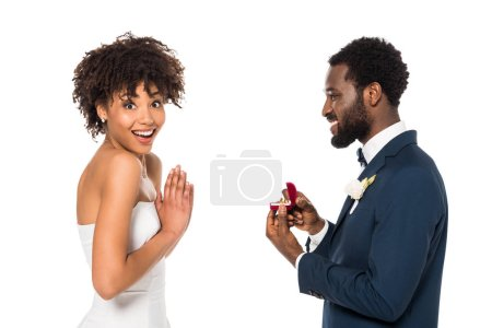Photo for Cheerful african american man holding box with ring while making proposal to surprised woman isolated on white - Royalty Free Image
