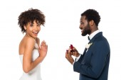 cheerful african american man holding box with ring while making proposal to surprised woman isolated on white