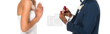 Photo for Panoramic shot of african american man holding box with ring while making proposal to  woman isolated on white - Royalty Free Image
