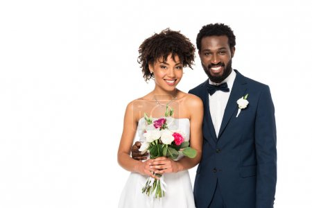 Photo for Happy curly african american bride smiling while holding bouquet near bridegroom isolated on white - Royalty Free Image