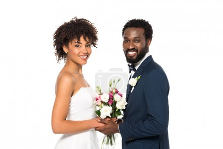 Photo for Cheerful african american bride holding bouquet near bridegroom and looking at camera isolated on white - Royalty Free Image