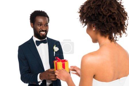 Photo pour Foyer sélectif de marié afro-américain heureux donnant cadeau à la mariée bouclée isolé sur blanc - image libre de droit