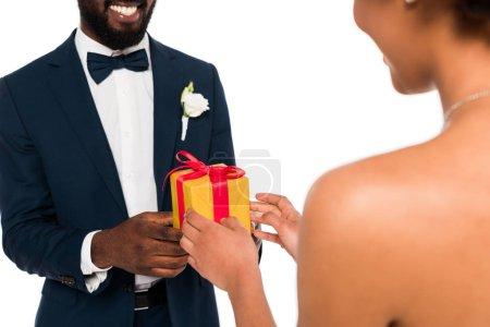 Photo pour Vue recadrée du marié afro-américain heureux donnant cadeau à la mariée bouclée isolé sur blanc - image libre de droit