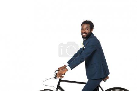 Photo pour Heureux marié afro-américain à vélo et regardant la caméra isolée sur blanc - image libre de droit