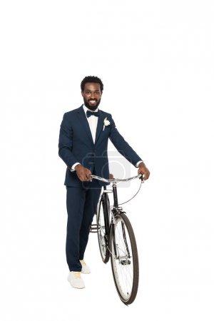 Photo pour Joyeux homme afro-américain en costume debout avec vélo isolé sur blanc - image libre de droit
