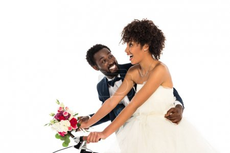 Photo for Happy african american bridegroom near cheerful bride with flowers riding bicycle isolated on white - Royalty Free Image