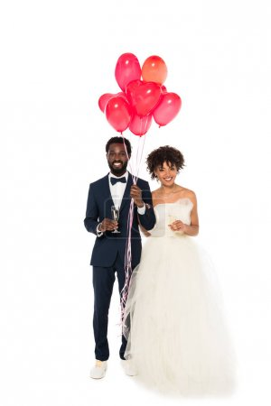 Photo for Cheerful african american bridegroom and bride holding champagne glasses near pink balloons  isolated on white - Royalty Free Image
