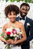 "Постер, картина, фотообои ""cheerful african american bride holding bouquet with flowers near bridegroom"""