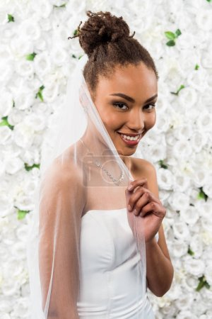 Photo for Happy african american bride touching white veil near flowers - Royalty Free Image