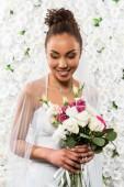 "Постер, картина, фотообои ""happy african american bride in veil holding bouquet of flowers """