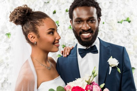 Photo for Happy african american bride looking at bridegroom holding flowers - Royalty Free Image