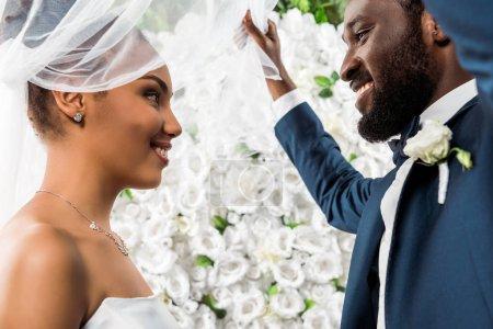Photo pour Vue à angle bas du marié afro-américain heureux touchant voile blanc et souriant près de la mariée et des fleurs - image libre de droit