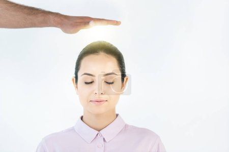 Photo for Cropped view of healer putting hand above head of attractive woman with closed eyes on white - Royalty Free Image
