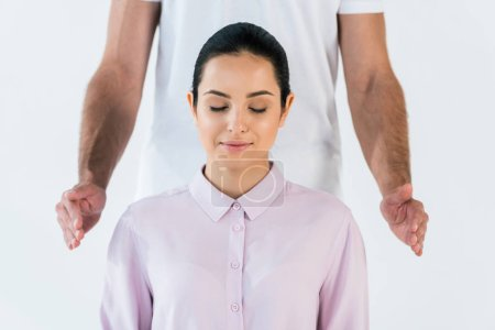 Photo pour Cropped view of healer putting hands near attractive woman with closed eyes isolated on white - image libre de droit