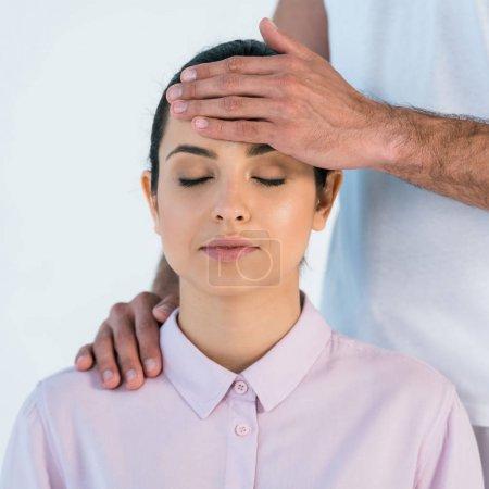 Photo pour Vue recadrée de l'homme mettant la main sur la tête de la femme attirante avec les yeux fermés isolés sur le blanc - image libre de droit