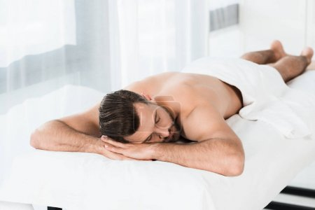 Photo pour Selective focus of handsome bearded man lying on massage table in spa center - image libre de droit