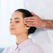 cropped view of man putting hands on temples of attractive woman with closed eyes