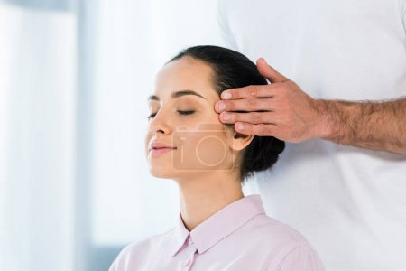 Photo for Cropped view of masseur putting hands on temples of woman with closed eyes - Royalty Free Image