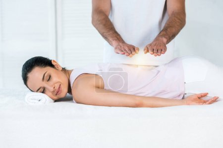 Photo for Cropped view of healer putting hands above attractive woman with closed eyes lying on massage table - Royalty Free Image