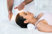 cropped view of healer putting hands near head of woman with closed eyes lying on massage table