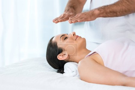 Photo pour Cropped view of man putting hands above head of attractive woman with closed eyes lying on massage table - image libre de droit