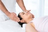 cropped view of healer putting hands near head of happy woman with closed eyes lying on massage table