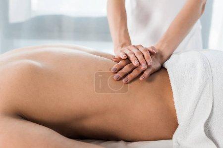 Photo pour Vue recadrée du masseur faisant le massage à l'homme torse nu se trouvant sur la table de massage - image libre de droit