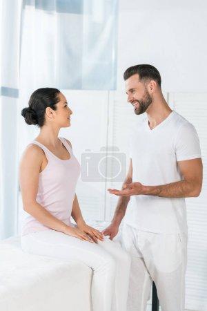Photo pour Gai masseur geste tout en regardant attrayant femme - image libre de droit