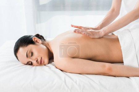 Photo pour Vue recadrée de masseur faire massage à attrayant brunette femme couché sur table de massage - image libre de droit