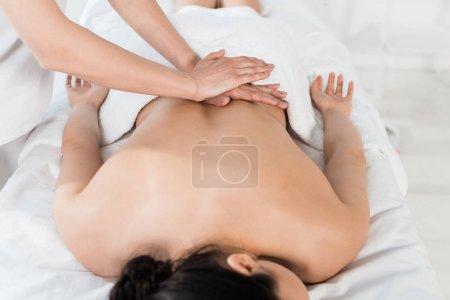 Photo pour Vue recadrée du masseur faisant le massage à la femme dans le centre de spa - image libre de droit