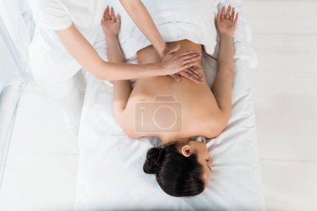 Photo pour Vue de dessus du masseur faisant massage à la fille brune couchée sur la table de massage - image libre de droit