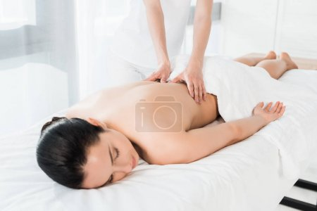 Photo for Cropped view of masseur doing massage to attractive brunette girl lying on massage table - Royalty Free Image