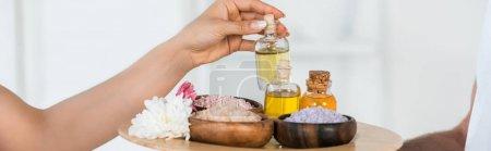 Photo pour Tir panoramique de la femme prenant la bouteille avec l'huile tandis que le plateau de fixation de masseur - image libre de droit