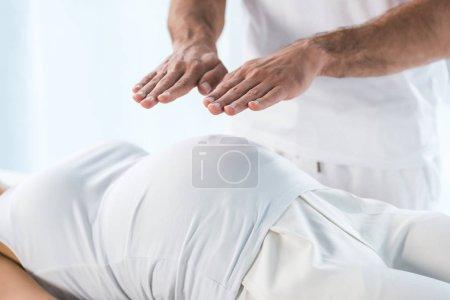 Photo pour Vue recadrée du guérisseur mettant les mains au-dessus du ventre de la femme enceinte - image libre de droit