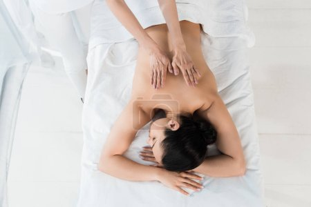 Photo for Top view of masseur doing massage to brunette girl lying on massage table in spa center - Royalty Free Image