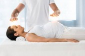 cropped view of man healing brunette pregnant woman lying on massage table