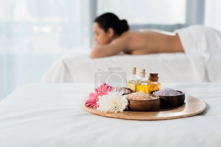 Photo pour Foyer sélectif du plateau avec des bouteilles d'huile, des cuvettes avec le sel de mer et les fleurs près de la femme brune dans le centre de spa - image libre de droit