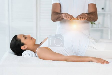 Photo for Cropped view of man healing attractive pregnant woman lying on massage table - Royalty Free Image