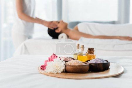 Photo pour Foyer sélectif de plateau avec des bouteilles d'huile, bols avec du sel de mer et des fleurs près des femmes dans le centre de spa - image libre de droit