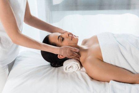 Photo pour Cropped view of masseur doing neck massage to attractive brunette woman lying on massage table - image libre de droit