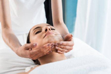 Photo pour Vue recadrée de masseur touchant le cou de jolie femme - image libre de droit
