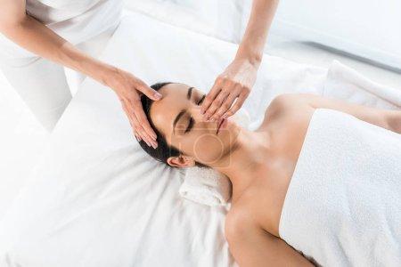 Photo pour Au-dessus du nez touchant de masseur de la femme brune attirante se trouvant sur la table de massage - image libre de droit