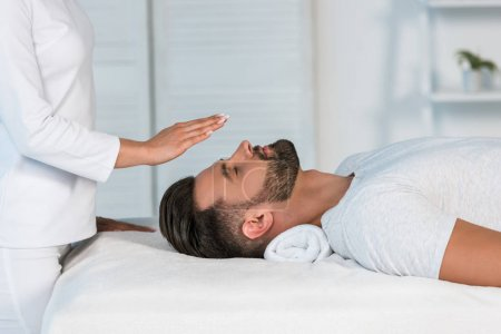Photo for Cropped view of healer putting hands above head of handsome man on massage table - Royalty Free Image